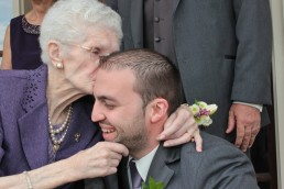 groom ceremony candid of grandmother kissing cheek in vermont
