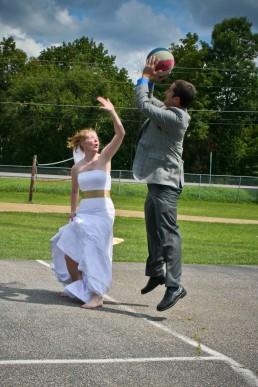 Wedding couple playing basketball at reception in wedding dress at Lake Bomoseen