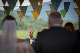 Groom's first look reaction with pinnies in foreground at Boyden Wedding Ceremony