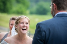 bride laughs during wedding ceremony at Boyden Farm in Vermont