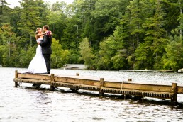 Candid kiss on the dock, a wedding portrait by Vermont wedding photographer