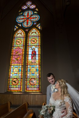 Church wedding portrait featuring stained glass window in Saint Albans, Vermont.