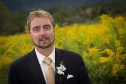 wedding groom portrait in field of yellow flowers in Vermont