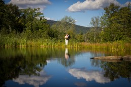 Wedding kiss couple portrait reflection with clouds at Mountaintop Inn in Vermont