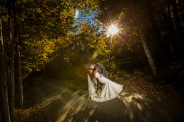wedding portrait in the fall featuring lens flare, and black bride in Stowe Vermont