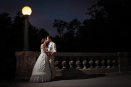 night wedding portrait under street lamp on bridge at Echo Lake Inn in Vermont