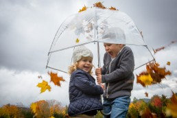 A candid lifestyle portrait featuring Vermont fall leaves and umbrella