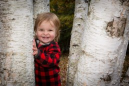 A lifestyle portrait of toddler playing peek a boo in Vermont fall trees.