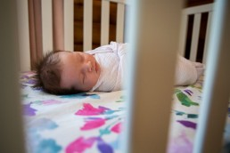 A lifestyle portrait of baby swaddled in crib sleeping
