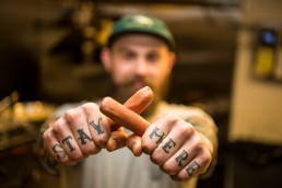 personal branding portrait of hands with tattoos holding hot dogs for restaurant