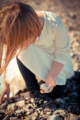 Lifestyle portrait candid of girl collecting rocks along Lake Champlain