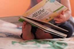 a personal branding image of a baby reading book with toes in Vermont
