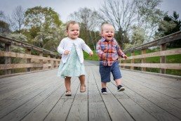 A lifestyle family portrait session of twins walking on bridge in Vermont