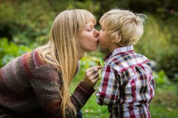 A candid lifestyle family portrait of mom and son kiss with flowers in Vermont