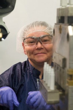 a personal branding image of a woman in a hairnet working at machine