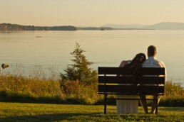 Sunset golden hour portrait of couple on bench overlooking Lake Champlain at Button Bay State Park