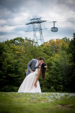 wedding couple dipping in front of Jay Peak tram in Vermont