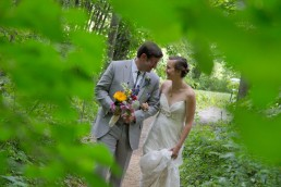 wedding portrait of couple walking through summer woods at Common Ground Center in Vermont