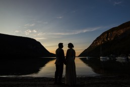 wedding couple silhouetted in sunset at Willoughby Lake, in Westmore, Vermont
