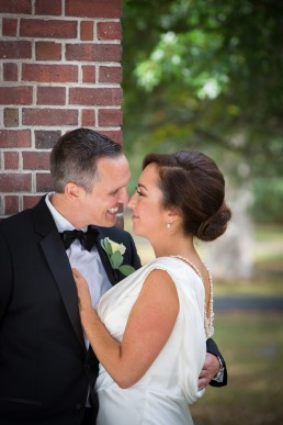 Candid wedding portrait along architectural brick wall by Vermont wedding photographers