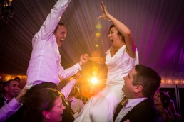 wedding dance party with colorful lights and people lifted up in air in Saratoga, New York