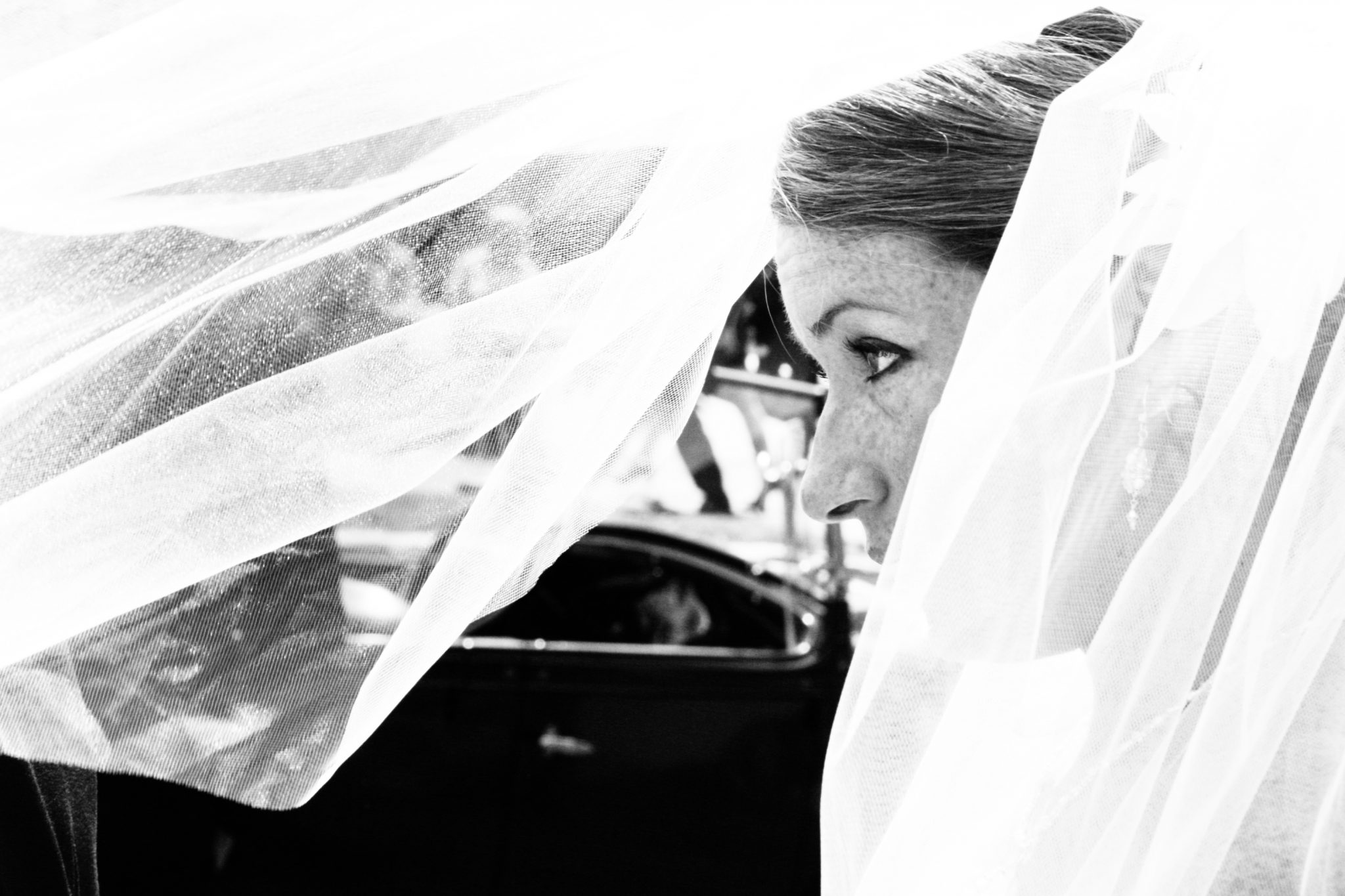 Black and white closeup of bride and veil in wind in Stowe, Vermont