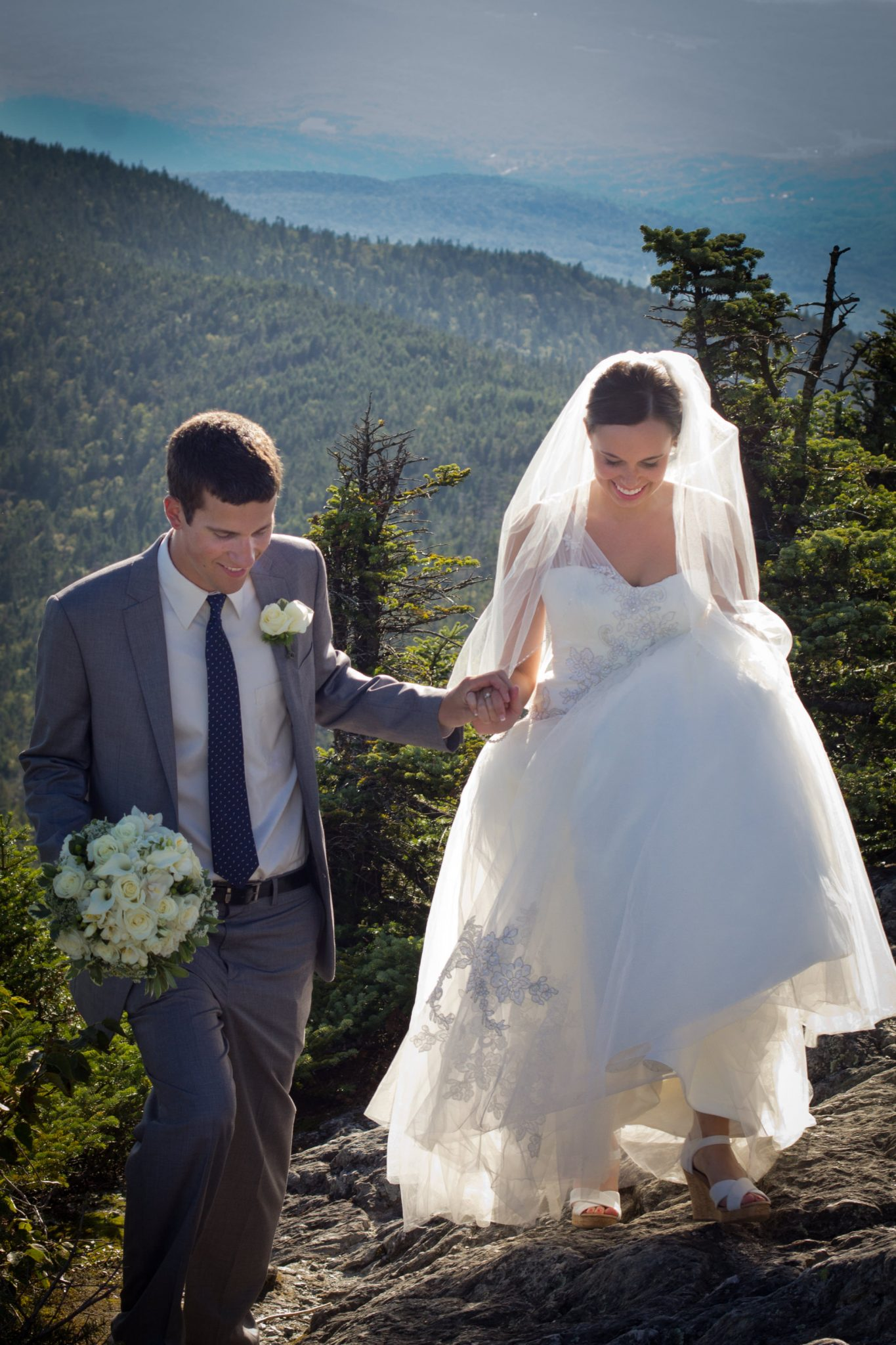 Couple climbs mountain at wedding candid portrait at Jay Peak in Vermont
