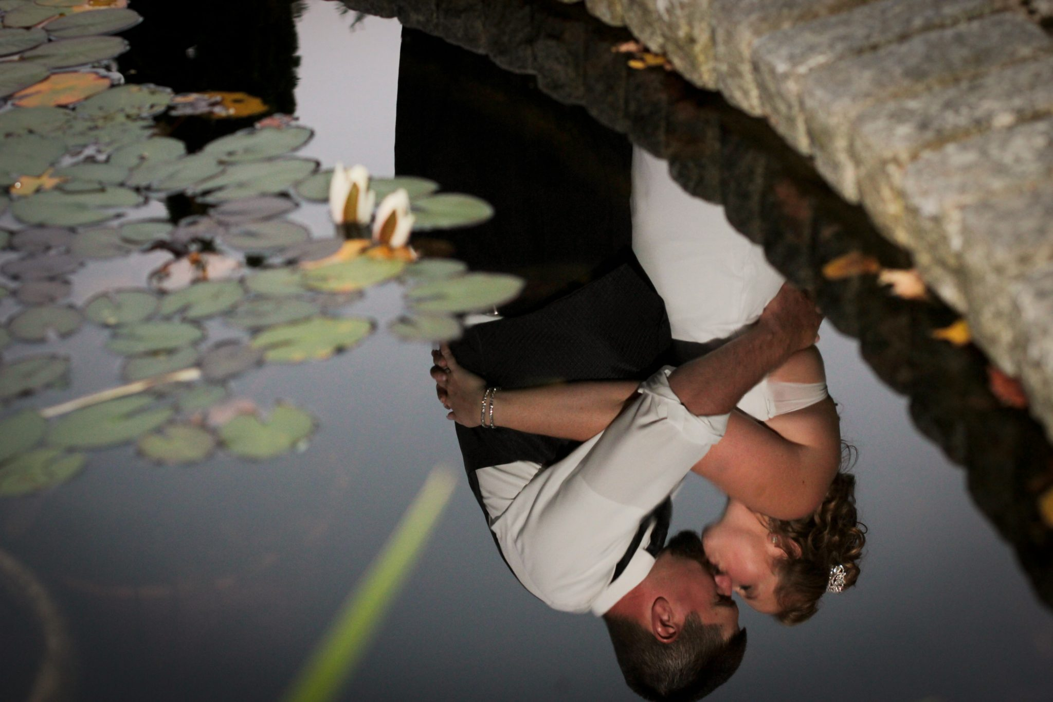 Wedding couple reflection in fish pond. Creative portrait at Lake Morey in Vermont