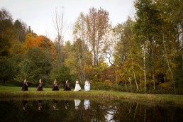 Fall wedding party group portrait with reflection in water at Moose Meadow lodge in Vermont