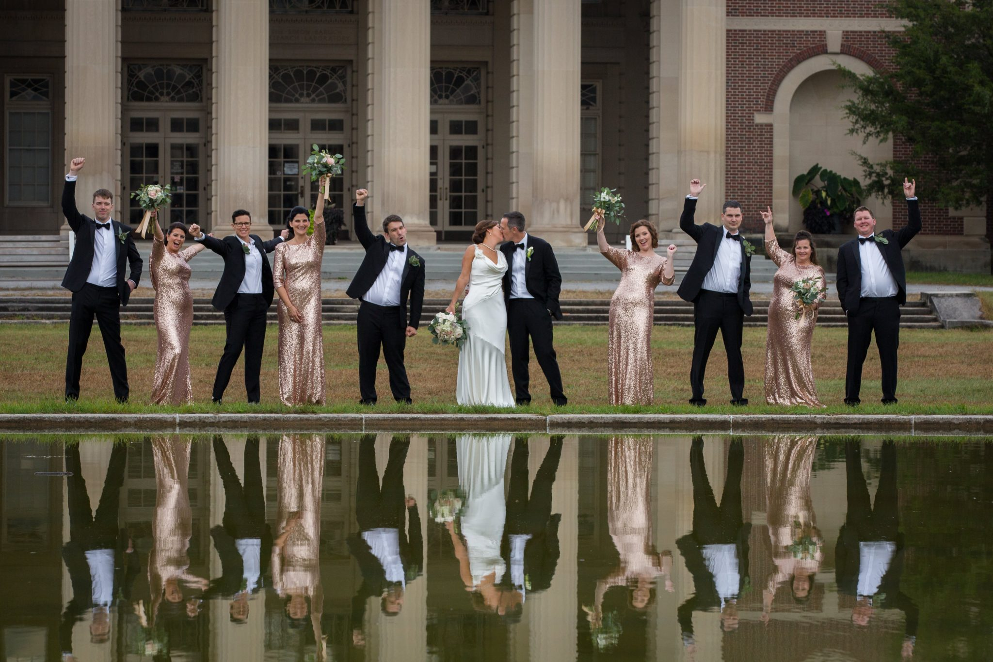 wedding party portrait fun with reflection on water and architectural brick by Vermont wedding photographers