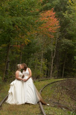 portrait in the fall of a gay wedding couple on train tracks by vermont wedding photographers