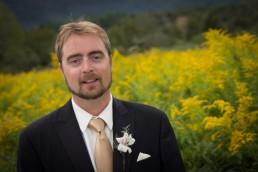 wedding groom portrait in field of yellow flowers in Vermont