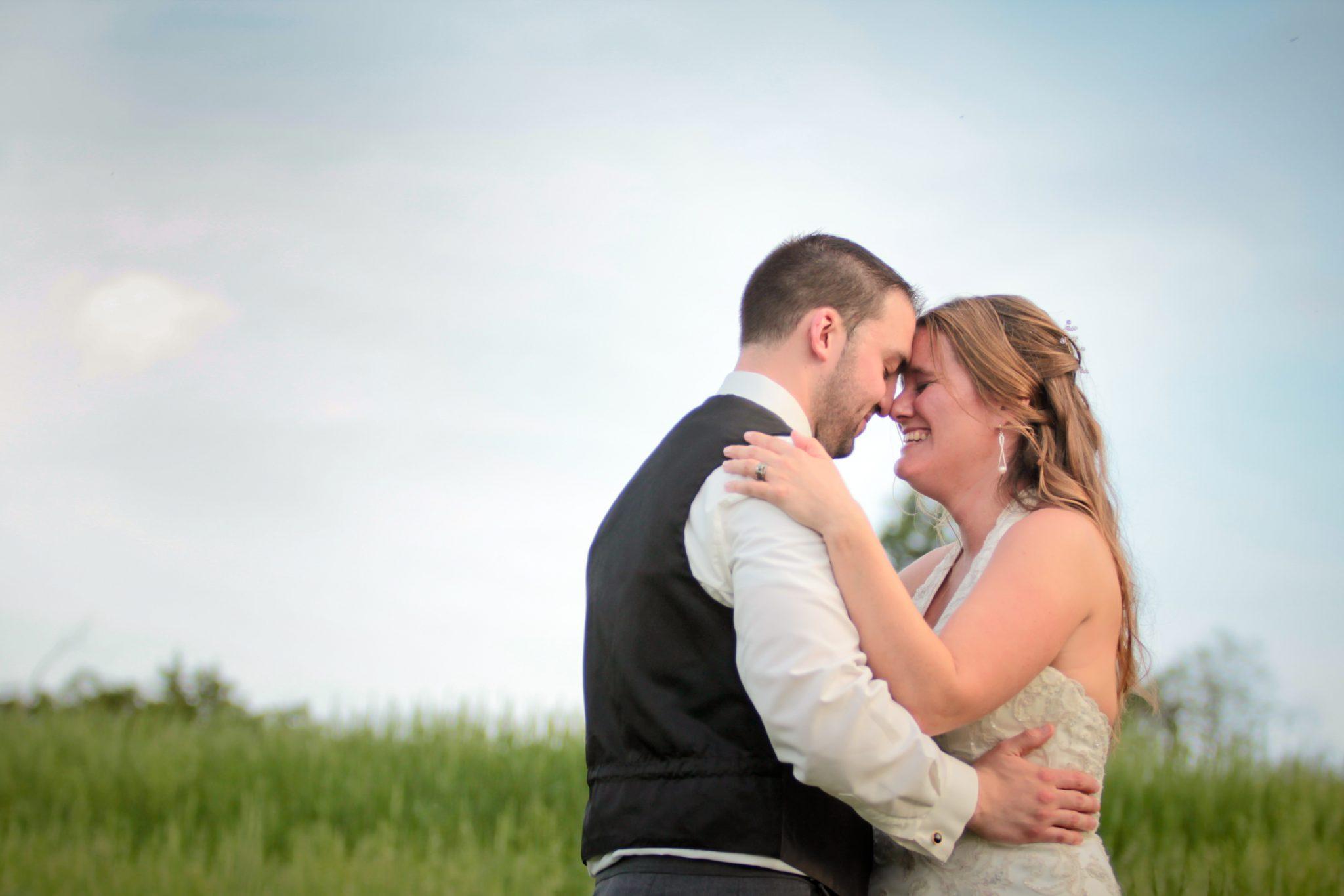 wedding couple in field portrait at Iron Lantern in Charlotte Vermont