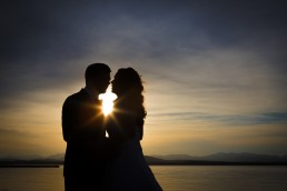 wedding portrait sunset silhouette with starburst on Lake Champlain in Vermont