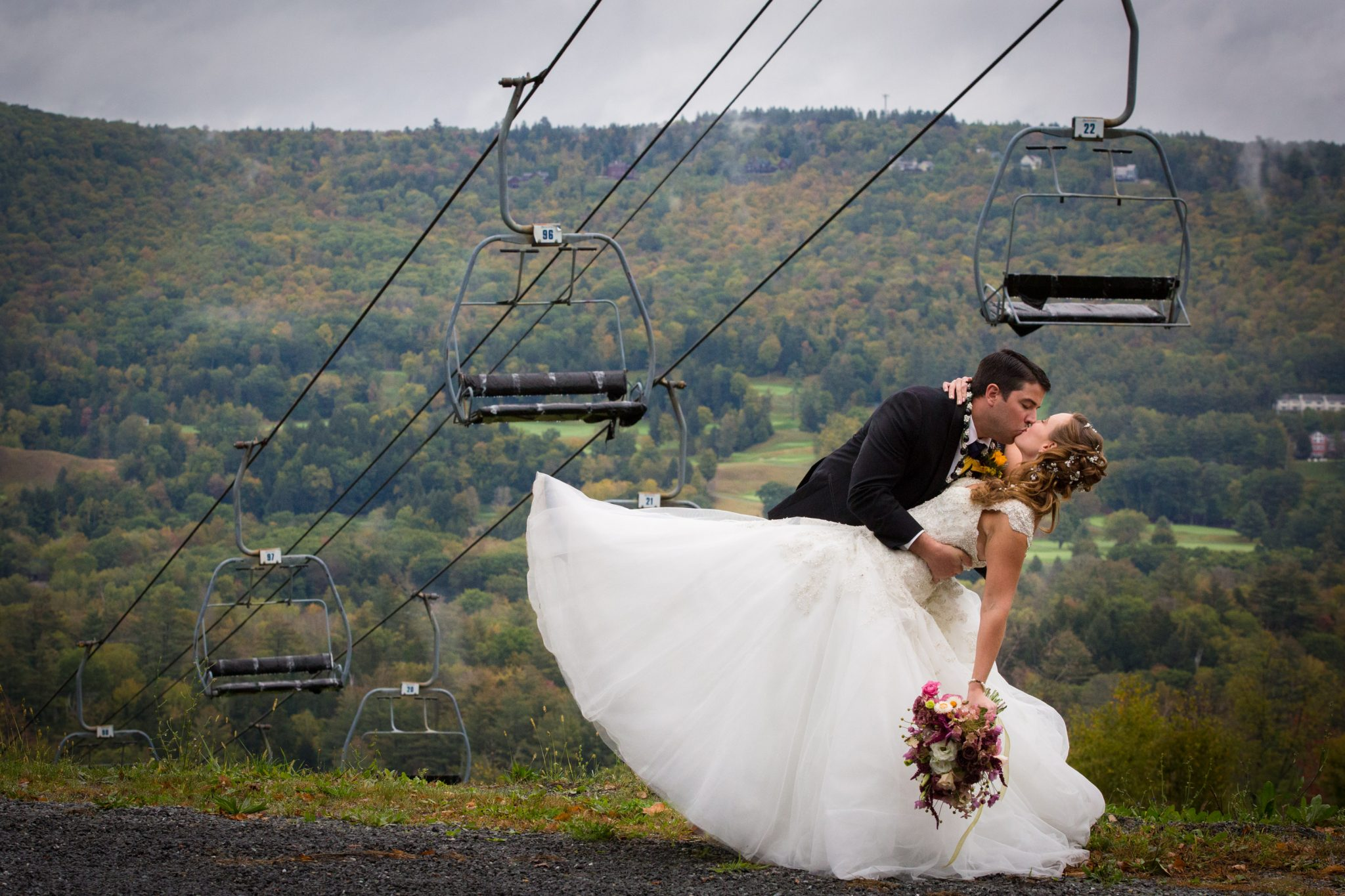 wedding couple dip in front of mountain chair lift at Okemo in Vermont