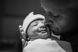 A black and white lifestyle portrait captured in the hospital of newborn baby