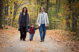 A lifestyle portrait of family walking through Vermont woods in the Fall.