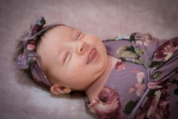 lifestyle newborn portrait of baby smiling with tongue.