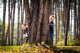 a lifestyle family portrait of kids playing peek a boo in Vermont