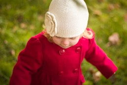 lifestyle family portrait of girl wearing red coat and cute hat in Vermont