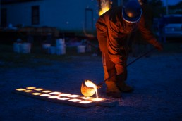 a personal branding image of a man pouring molten metal into molds at night