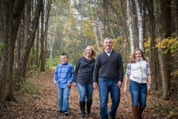 lifestyle family candid portrait of family walking in fall woods in Vermont