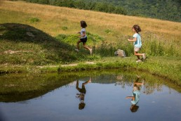 A lifestyle family portrait of kids reflection running along pond in Hubbardton
