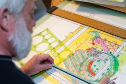 a personal branding image of landscape architects hands at desk with plan