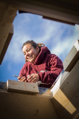 personal branding image of woman carpenter working on roof through sky light for Yestermorrow