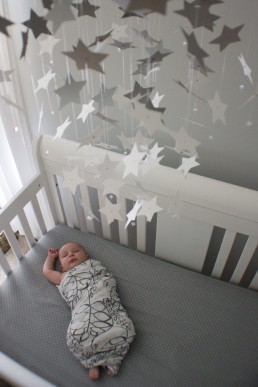 A lifestyle baby portrait sleeping in crib with stars above