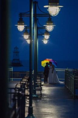 Rainbow umbrella portrait of gay wedding couple on Lake Champlain in Vermont