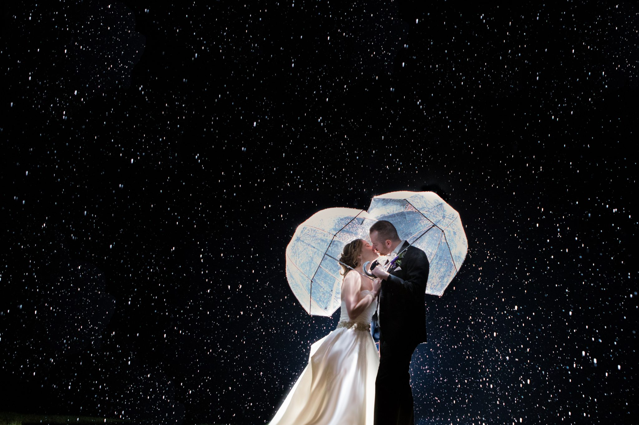 Rainy wedding portrait with umbrellas as night at Mountaintop in Vermont