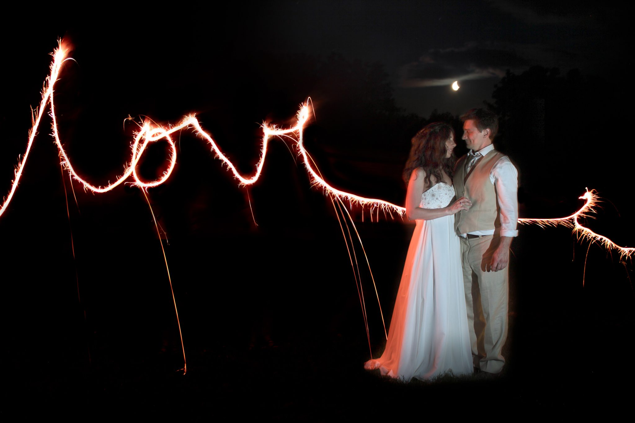 Sparklers write out love behind wedding couple night photograph in Vermont