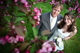 Spring wedding couple below tree blossoms by Vermont Wedding photographers